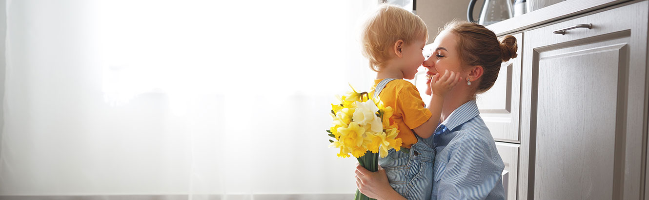 A woman and her son hugging while the woman holds flowers her son gave her.