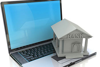 A model of a bank sitting on a laptop.